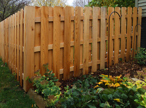 Long, natural colored fence around house.